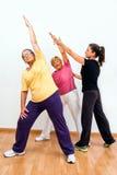 Monitor del gimnasio que ayuda a señoras mayores con ejercicio Imagenes de archivo