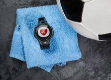 Monitor del ritmo cardíaco en la toalla azul cerca del balón de fútbol imagenes de archivo
