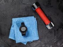 Monitor del ritmo cardíaco en la toalla azul cerca del balón de fútbol foto de archivo