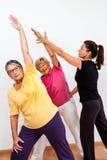 Monitor di forma fisica che aiuta le signore senior nella classe Immagine Stock Libera da Diritti