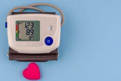 Monitor elettronico moderno di pressione sanguigna con cuore rosso su un fondo blu immagini stock libere da diritti
