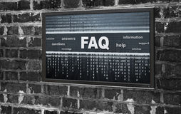Monitor with FAQ on a screen. Monitor with FAQ message hanging on dirty brick wall stock photos