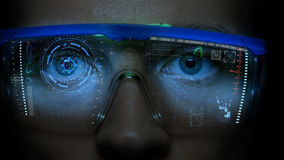 Monitor futurista en cara con el holograma del código y de la información Animación del hud del ojo Concepto futuro Fotos de archivo libres de regalías