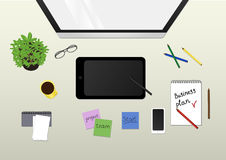 Monitor, graphic tablet, plant, coffee, phone and office supplies on the desktop. view from above Stock Image