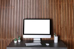 Monitor moderno do computador na mesa contra a parede de madeira foto de stock