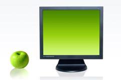 Monitor y manzana verde Fotografía de archivo