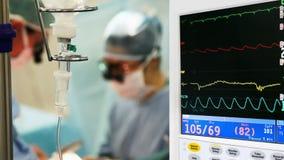 Monitoração na sala de operação com os cirurgiões no fundo vídeos de arquivo