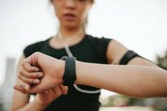 Monitoraggio femminile di forma fisica la sua prestazione su smartwatch Fotografia Stock Libera da Diritti