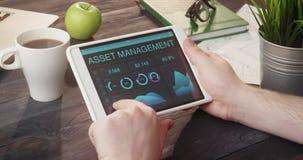 Monitoring asset management data using tablet computer at desk. Monitoring asset management data using tablet computer at the desk stock video