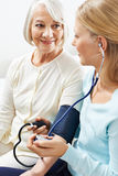 Monitoring blood pressure for senior woman Royalty Free Stock Photography