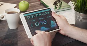 Monitoring cost per click records using digital tablet at desk stock footage