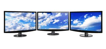 Monitors. Computer wide monitors or TV in a panoramic set with a sky wallpaper on a screen. Isolated on a white. 3d image Royalty Free Stock Photography