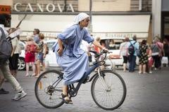 Monja de la hermana que completa un ciclo en las ciudades En la bicicleta Fotos de archivo libres de regalías