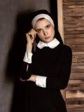 Monja hermosa joven humilde en los hábitos que llevan a cabo una cruz en un fondo gris Fotografía de archivo