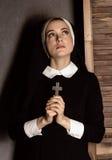 Monja hermosa joven humilde en los hábitos que llevan a cabo una cruz en un fondo gris Foto de archivo