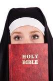 Monja joven con la biblia aislada Foto de archivo
