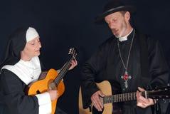 Monja y sacerdote con la guitarra Foto de archivo libre de regalías