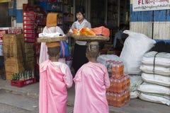 Monjas birmanas que recogen limosnas de la mañana imagenes de archivo