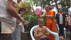 Monje budista que afeita la cabeza de un muchacho para prepararlo para el novato