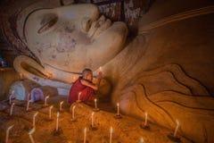 Monje del budismo que ruega con la luz de la vela en el templo de Shwesandaw Fotos de archivo libres de regalías