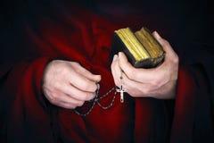 Monje del misterio con un cabo que sostiene biblias y un rosario negro Fotografía de archivo