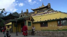Monje delante de uno de los stupas cerca del monasterio de Gandan en Ulaan Bataar, Mongolia almacen de video
