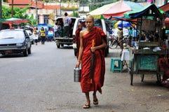 Monje joven que recorre en Yangon con el almuerzo de ofrecimiento Imagen de archivo libre de regalías