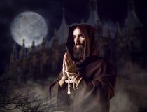 Monje medieval que ruega contra castillo y la Luna Llena fotografía de archivo libre de regalías