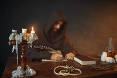 Monje medieval que se sienta en la tabla y escribir, visión superior fotografía de archivo libre de regalías