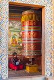 Monje que ruega en una casa de la rueda de rezo - Bhután imagen de archivo