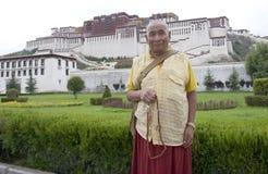 Monje tibetano delante del palacio de Potala Imagenes de archivo