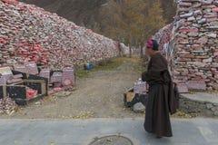 Monje tibetano que camina delante de la pared de piedras de Mani con el mantra budista OM Mani Padme Hum grabado en tibetano en Y Foto de archivo libre de regalías