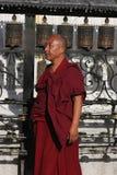 Monje y ruedas de rezo tibetanos Fotografía de archivo