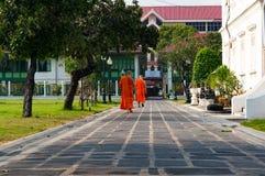 Monjes budistas del novato en traje anaranjado brillante que caminan ocasional Imagenes de archivo