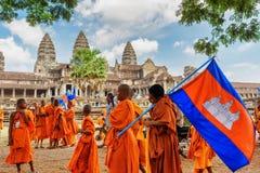 Monjes budistas jovenes con la bandera nacional de Camboya en Angkor Fotografía de archivo libre de regalías