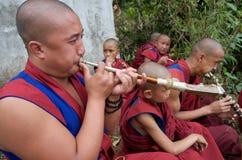 Monjes budistas jovenes que juegan los claxones fotos de archivo