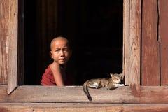 Monjes budistas jovenes que se ríen de una ventana Fotos de archivo