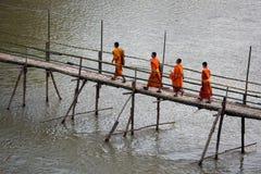 Monjes budistas que cruzan el puente de bambú en Luang Prabang, Laos Imagen de archivo