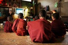 Monjes budistas que disfrutan de la show televisivo Fotografía de archivo