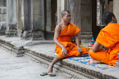 Monjes camboyanos que se sientan en las escaleras en el templo de Angkor Wat, Camboya Foto de archivo libre de regalías
