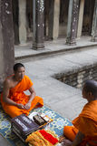 Monjes camboyanos que se sientan en las escaleras en el templo de Angkor Wat, Camboya Foto de archivo