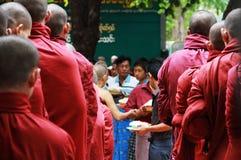 Monjes de Myanmar que esperan la comida diaria Foto de archivo