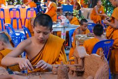 Monjes jovenes budistas en el wat del templo de Tailandia que hace artes de la mano Fotos de archivo