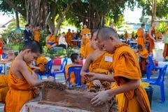 Monjes jovenes budistas que hacen artes de la mano en la yarda del templo Imagenes de archivo