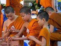 Monjes jovenes budistas que hacen artes de la mano en la yarda del templo Fotos de archivo libres de regalías