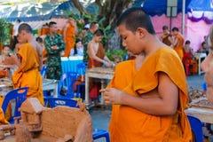 Monjes jovenes budistas que hacen artes de la mano en la yarda del templo Fotos de archivo