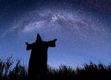 Monk against starry night sky. Silhouette of monk with raised hands against starry night sky with wonderful milky way Royalty Free Stock Image