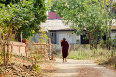 A monk in Bagan, Myanmar. A monk walking on village lane in Bagan, Myanmar. Bagan is an ancient city located in the Mandalay Region of Myanmar . From the 9th to Stock Images