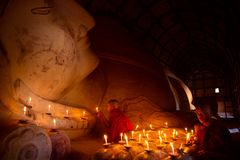 Monk in Bagan old town pray a buddha statue with candle stock photos