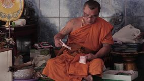 Monk in Bangkok. MOnk in the Bangkok temple counting money from donations stock footage
